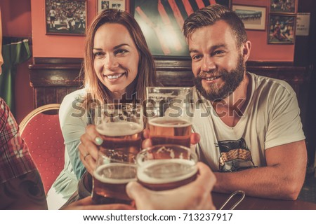 Good old friends drinking beer in a pub #713237917