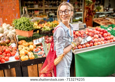 Young woman using smartphone standing with bag in front of the food market in France #713274235