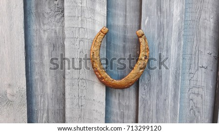 The antique horseshoe on the old wooden fence texture. #713299120