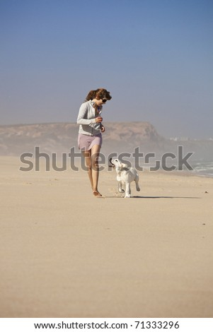 Young woman running and playing with her cute labrador retriever puppy #71333296