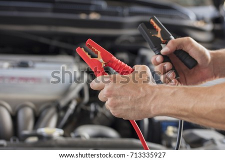 Charging car battery from another car with a set of jumper cables #713335927