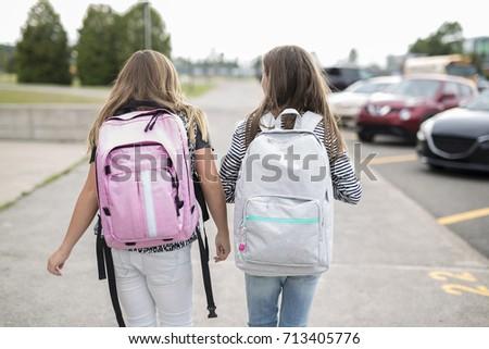 Portrait of two pre teenage girls studying outdoors in school yard left school