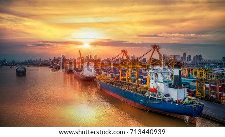 Logistics and transportation of Container Cargo ship and Cargo plane with working crane bridge in shipyard at sunrise, logistic import export and transport industry background #713440939
