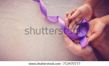Hands holding Purple ribbons, toning copy space background, Alzheimer disease, Pancreatic cancer, Epilepsy awareness, domestic violence awareness,fibromyalgia awareness, world cancer day #713470777