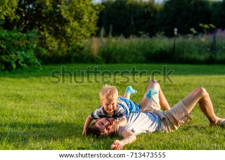 Happy man and child having fun outdoor on meadow.  Family lifestyle scene of father and son resting together on green grass in the park.  #713473555