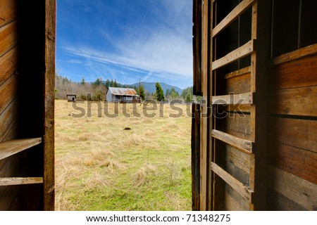 View from inside of the barn to the farm land with shed and field. Build in 1907 diary farm near Mt. Ranier in Washington State #71348275