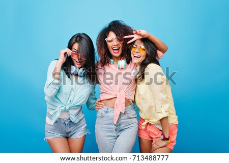 Cute international female friends in colorful shirts embracing while posing with smile on blue background. Cheerful brunette girl in denim shorts holding glasses and laughing beside university mates.