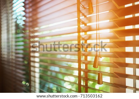 Wooden blinds with sun rays. Royalty-Free Stock Photo #713503162