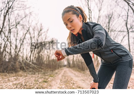 Sport watch run woman checking smartwatch tracker. Trail running runner girl looking at heart rate monitor smart watch in forest wearing jacket sportswear. Female athlete jogger training in woods. #713507023