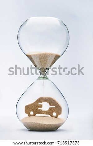 Time for clean energy concept with falling sand taking the shape of an electric car inside a hourglass #713517373