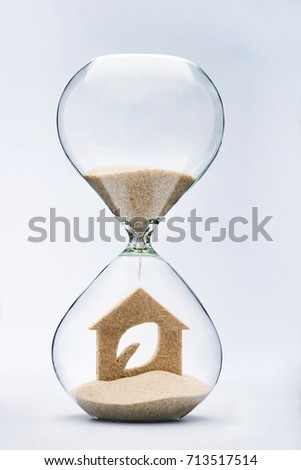 Time for clean energy concept with falling sand taking the shape of an eco house inside a hourglass #713517514