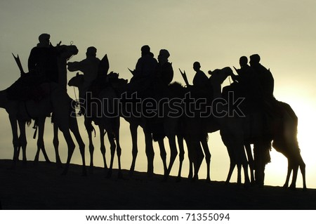 A silhouette of a group of Tuareg on their camels in the desert #71355094