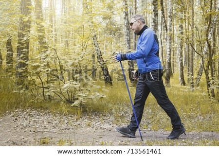 adult man is engaged in nordic walking in the park #713561461