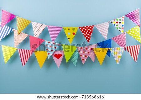 Birthday fest garlands from colorful triangular flags on blue background