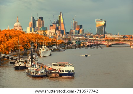 London, view over river Thames on St. Paul's cathedral and Blackfriars bridge with Sun reflected in tall buildings of the London skyline behind, toned image. #713577742