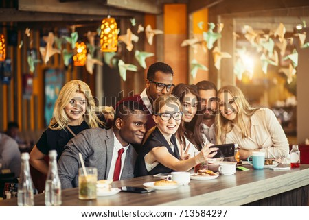 Group of happy smiling people taking a self-portrait in a cafe white having a break #713584297