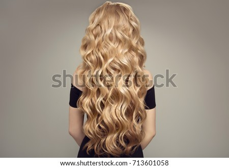 Blond woman with long curly beautiful hair. Back view.  #713601058