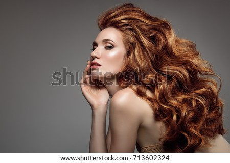Portrait of woman with long curly beautiful ginger hair.  #713602324