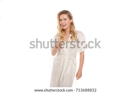 young blonde woman in robe showing thumb up and smiling at camera isolated on white #713688832