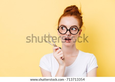 Surprised ginger woman in eyeglasses holding dividers and looking away over yellow background #713713354