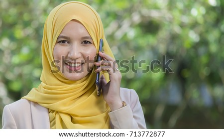 Beautiful businesswoman in hijab talking on cell phone and looking to camera #713772877