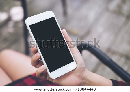 Mockup image of a woman's hand holding white mobile phone with blank black screen on thigh with wooden floor background in vintage cafe #713844448