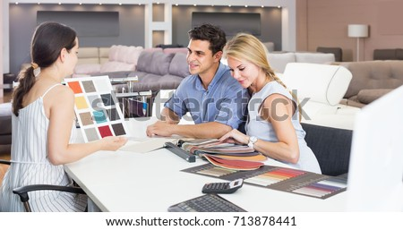 couple are consulting with seller about the colors of furniture in furniture store #713878441