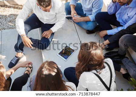 Coworkers group sitting outside watching something on tablet #713878447