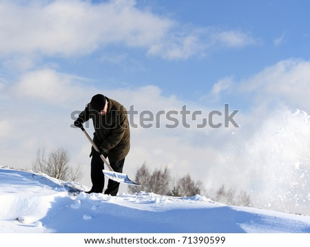 A man with a shovel removing snow from a driveway #71390599