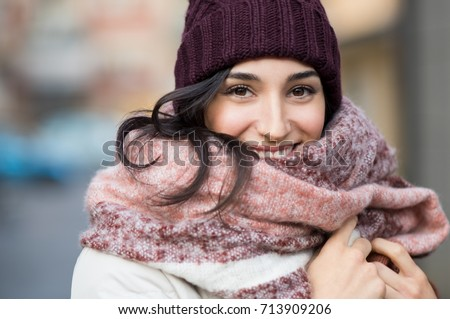 Closeup face of a young happy woman enjoying winter wearing scarf and cap. Smiling girl in a colorful shawl looking at camera. Latin woman with knitted bordeaux hat and woolen scarf. #713909206