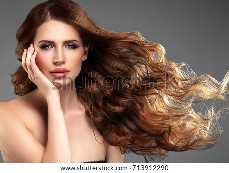 Beauty Woman face Portrait. Beautiful model Girl with Perfect Fresh Clean Skin. Brunette female looking at camera and smiling on dark background. Beautiful hairstyle  #713912290