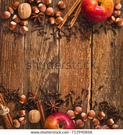 Red apples, nuts, anise, clove and cinnamon on a old wooden background.   #713940868
