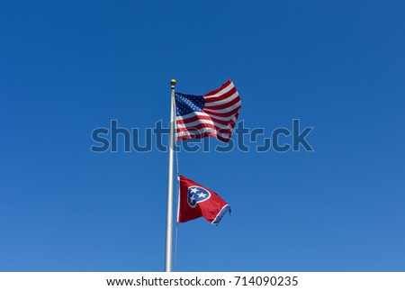 Picture of Tennessee State Flag and American Flag on a flagpole with clear blue skies