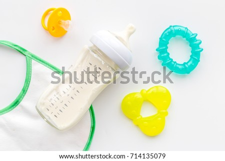 bottle with breastmilk and infant formula powdered healthy food, toys and bib on white background top view #714135079