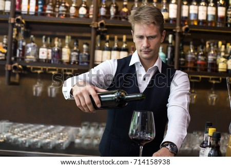 Handsome sommelier man Pour wine to the glass in restaurant, Man present Wine to Customer, Man with Sommelier Concept. #714158938