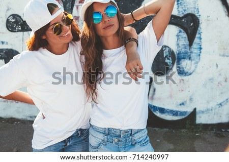 Two models wearing plain white t-shirts and hipster sunglasses posing against street wall. Teen urban clothing style, same look. Mockup for tshirt print store.  #714240997