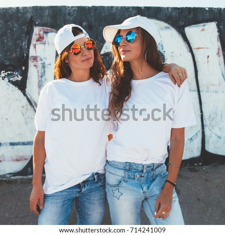 Two models wearing plain white t-shirts and hipster sunglasses posing against street wall. Teen urban clothing style, same look. Mockup for tshirt print store.  #714241009