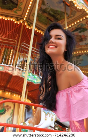 Festive young girl in front of carousel wearing pink dress. #714246280