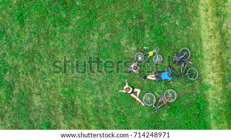Family cycling on bikes outdoors aerial view from above, happy active parents with child have fun and relax on grass, family sport and fitness  #714248971