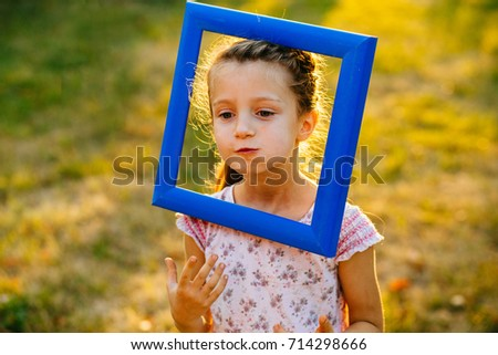 Cute preschooler girl with blue frame on her head playing over grass in sunset in autumn time. Art, drawing and kids creativity concept.