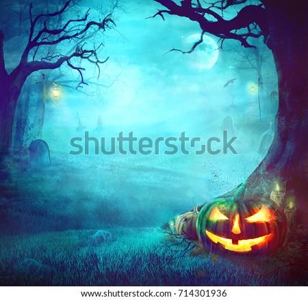 Halloween Pumpkin in Dark Forest. Halloween Background. Halloween Pumpkin with Graveyard Royalty-Free Stock Photo #714301936