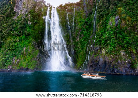 Tourist ferry carrying people approaching Stirling Falls at Milford Sound in South Island of New Zealand. Royalty-Free Stock Photo #714318793