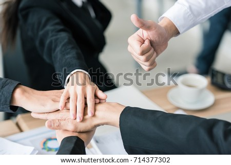 Successful young business people teamwork, giving thumb up and united hands or joining hand together for stronger team. #714377302