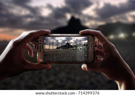 Photo camera of a smartphone. View through the screen at the time a young woman takes a photo of Rio de Janeiro city at night. Ipanema beach. Cityscape. Landscape.