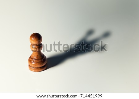 trust yourself, self confident concept - chess pawn with king shadow Royalty-Free Stock Photo #714451999