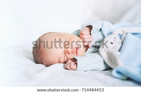 Newborn baby sleep first days of life. Cute little newborn child sleeping peacefully Royalty-Free Stock Photo #714484453