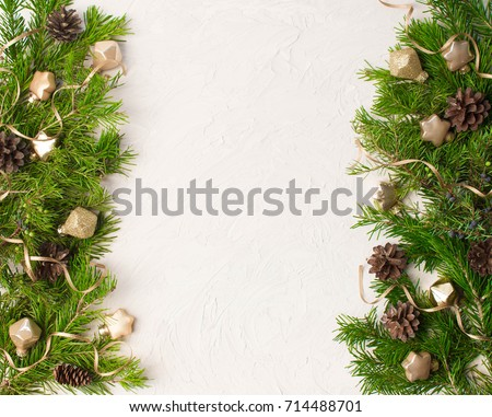Christmas or New Year background: fur-tree, branches, gifts, colored glass balls and toy, decoration and cones on a white plaster background #714488701