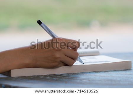 Young girl writes on a book, education or business concept #714513526
