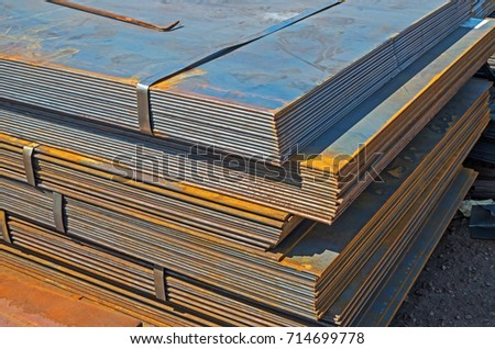 The rusty hot-rolled sheet metal in packs at the warehouse of metal products piled in the open air #714699778
