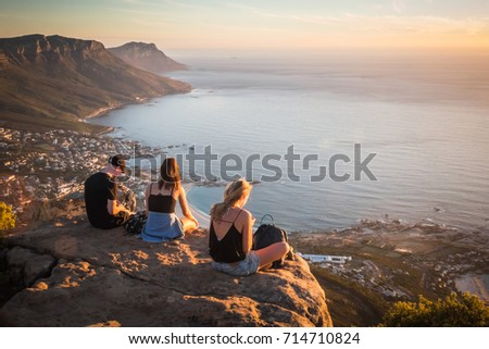Young man and women sitting on the rock on top of Lion's head mountain look at the Atlantic Ocean and Cape town city view in South Africa #714710824